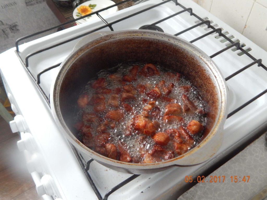На фото: обжарка свинины для приготовления плова