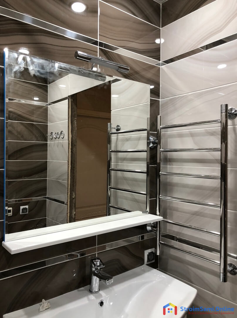 На фото: зеркало, полка и полотенцесушитель в ванной комнате