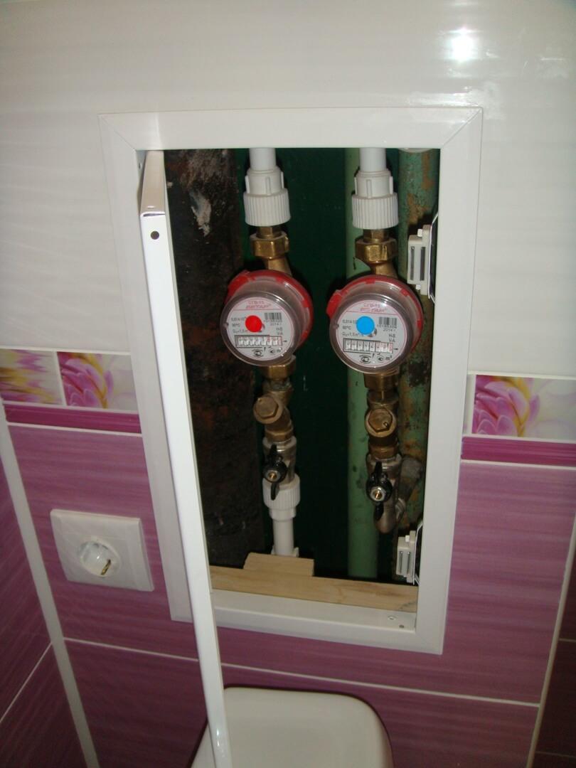 На фото: трубы и счетчики воды, спрятанные в стене