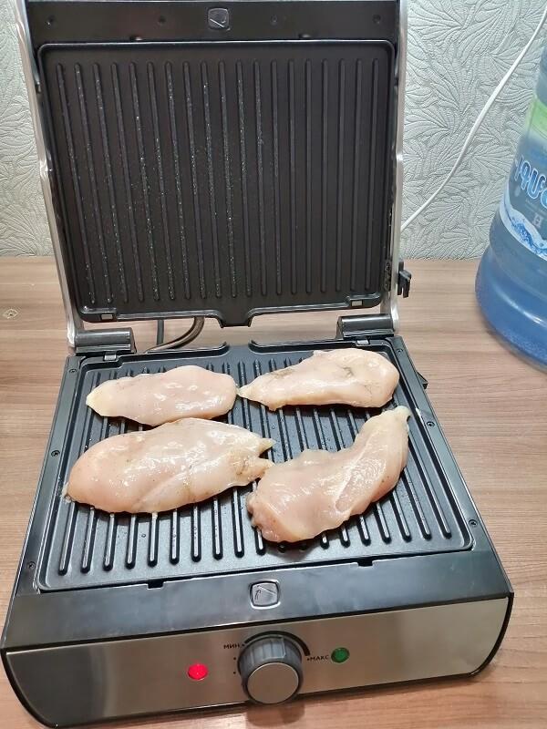 На фото: приготовление куриной грудки на электрогриле
