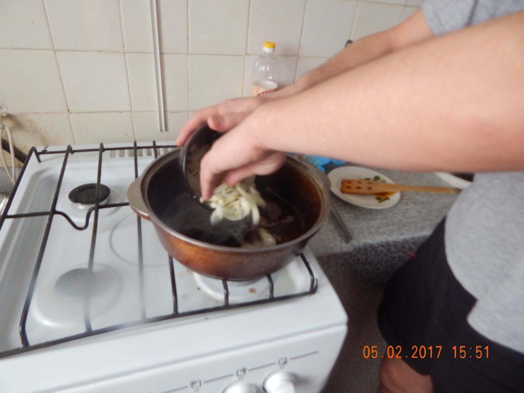 На фото: обжарка лука для приготовления плова