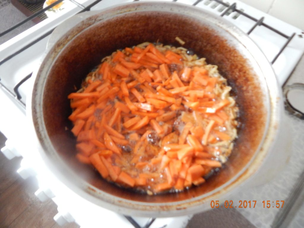 На фото: обжарка лука и моркови для приготовления плова