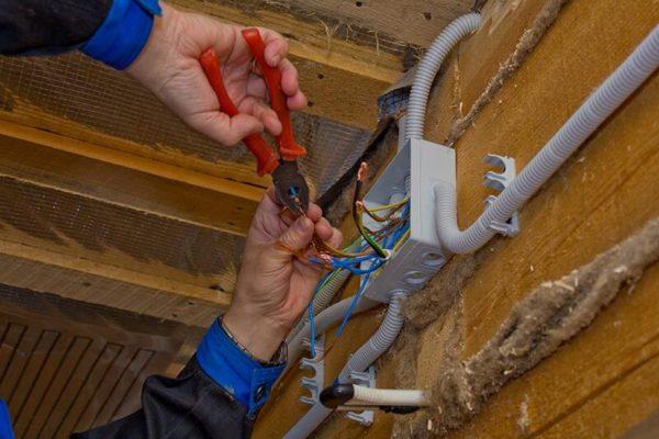 На фото: монтаж наружной электропроводки на деревянной поверхности